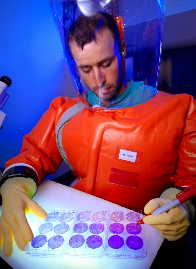 A scientist in a biocontainment suit counting viral plaques.