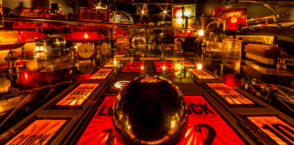 """A close up image of a ball inside brightly lit pinball machine."