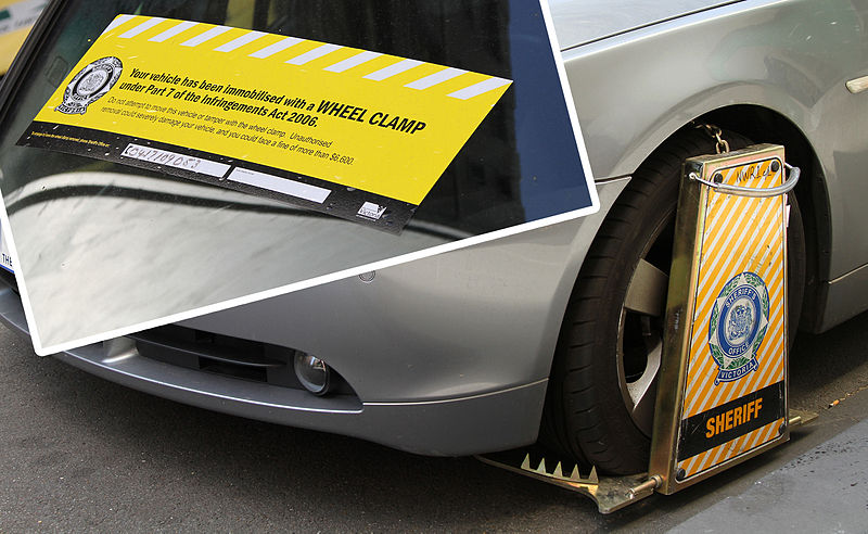 A car with signs warning people not to steal its parts.