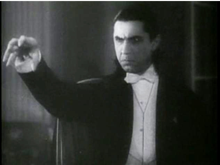 Bela Lugosi, as Dracula, raising his hand ominously.