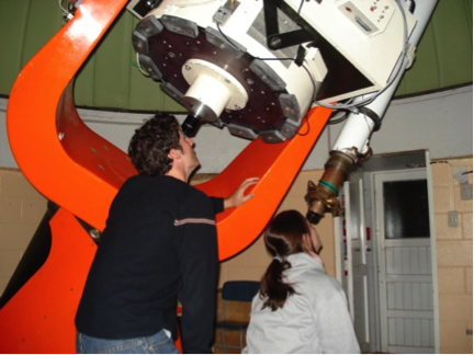 Two people peek into a giant telescope pointed at the sky.