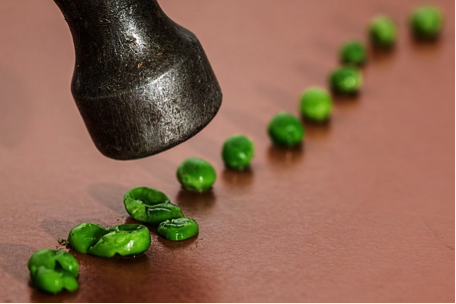 The metal end of a hammer, smashing a line of green peas, one by one.